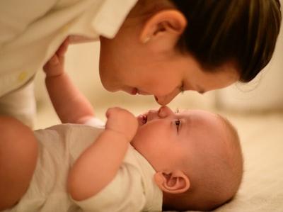 赤ちゃんと触れ合うママ