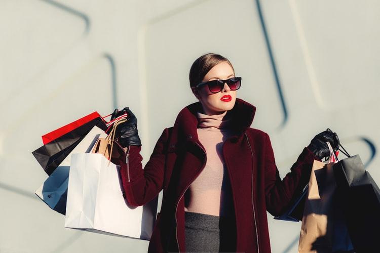 コスメや服のショッピングバッグをたくさん持つ女性