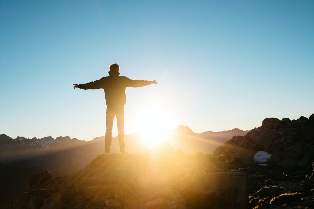 山頂で日の光を浴びる男性