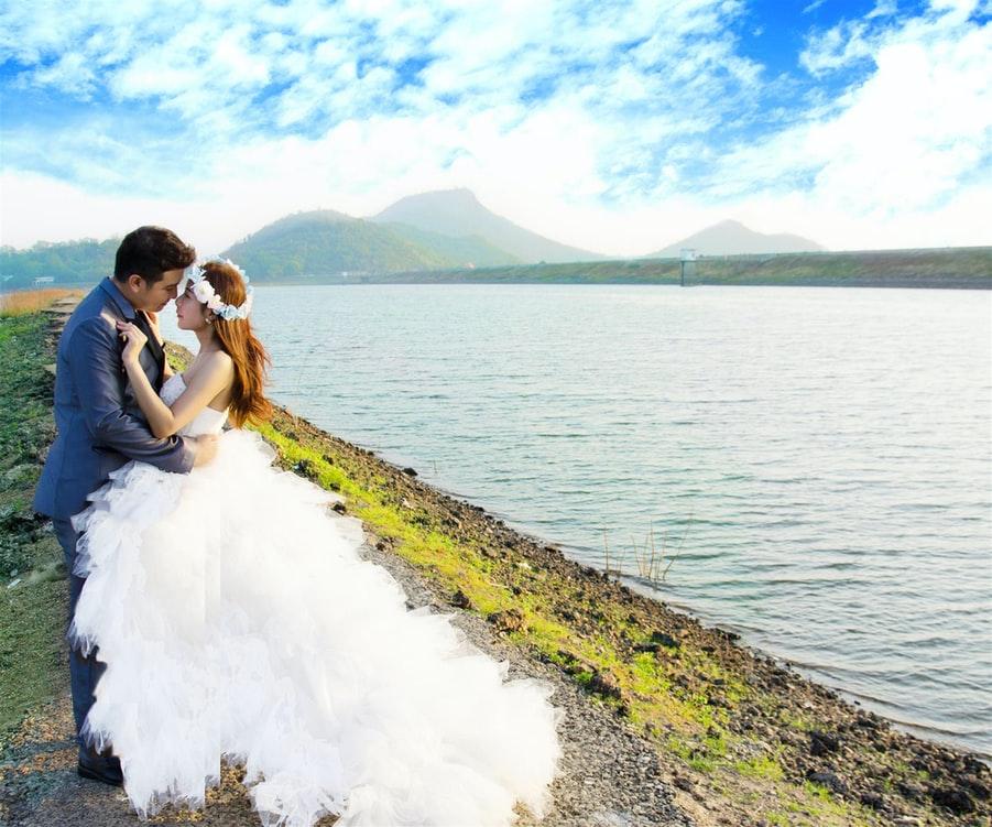 海辺で見つめ合う新婚夫婦