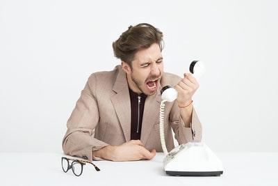 電話に向かって怒鳴る男性