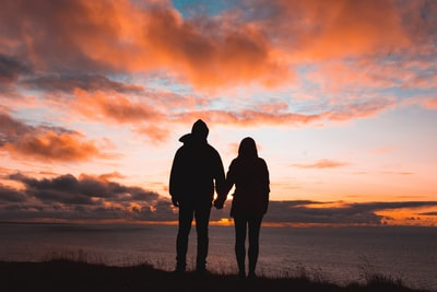 夕暮れ時に手をつなぐカップル
