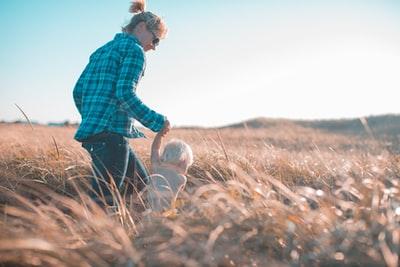草原で手をつなぐママと子どもども