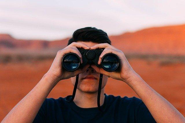 双眼鏡で遠くを見る人